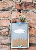 Bilderrahmen mit Kronen und Kaktus hängt an Backsteinwand