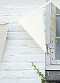 Aus Stoff genähte Wimpelkette an weißer Backsteinwand