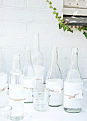 Clear glass bottles wrapped in torn fabric