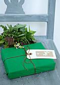 Grün verpacktes Geschenk mit Anhänger und Strauß aus dem Garten