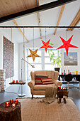 Comfortable armchair below star decorations in festive open-plan interior
