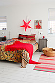 Colourful bedspread and red fringed blanket on double bed below red, star-shaped lamp on wall