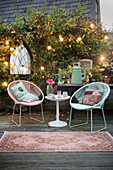 Retro easy chairs and side table on terrace surrounded by plants and fairy lights