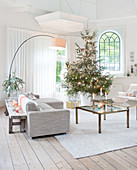 Christmas tree in bright living room with sofa, coffee table and wooden floor
