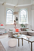Sofa, set of coffee tables and arc lamp in front of arched windows in living room with woman in background