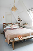 Wooden bench at foot of bed with patchwork quilt below sloping ceiling