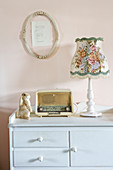 Old-fashioned table lamp and old radio on pale blue cabinet