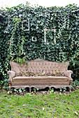 Altes Sofa vor der Gartenmauer mit Efeu und Bilderrahmen