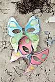 Homemade masks with butterfly motifs in the sand