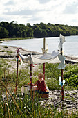 Child sits under a canopy with butterfly decorations on the beach and does handicrafts