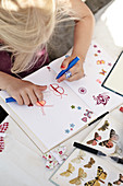 Girl paints butterflies in a notebook