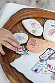 Children's hands tinker with stones, stickers and butterfly motifs