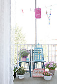 Blaue Stühle und Blumen auf dem Balkon