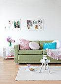Romantic pillows on the green sofa under two mood boards