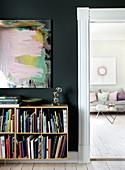 Bücherregal an schwarzer Wand, Blick ins Wohnzimmer in Pastellfarben