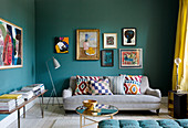 Picture gallery above the sofa in the living room with petrol blue walls