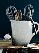 Kitchen utensils in a rustic pitcher, salt in wooden bowls