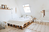 Bedroom in natural tones under the eaves of a sloping roof with pallet bed