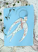 Aus Landkarte ausgeschnittene Schwalbe auf blauem Papier