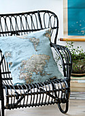 Homemade pillow with map motif on a black rattan chair