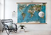 Schwarzer Rattanstuhl vor einer Weltkarte im Vintage-Stil