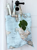 Fabric bag with a world map motif and rolled up maps