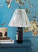 Homemade lamp from a bottle with a lampshade made from a folded map