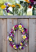 Blumenkranz und Sträußchen in Wassergläsern an einer Bretterwand