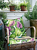 Cushions with a funky motif on a rattan chair