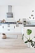 Simple white kitchen with black handles and gray worktop