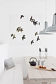 Wall decoration with a bird motif above the light wooden table