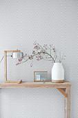 Tischleuchte und Vase mit Hagebuttenzweig auf Konsolentisch vor gemusterter Tapete