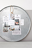 A silver metal tray as a pinboard with winter postcards