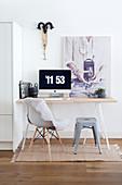 Computer mit Uhrzeit auf dem Schreibtisch mit Stuhl und Hocker