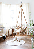 Macrame hanging chair above the round carpet