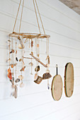 Mobile made of shells and driftwood in front of a white plank wall