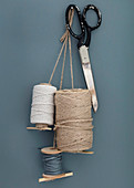 spools and scissors hanging on the wall