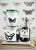 Etiketten mit Schmetterling-Motiv auf Schraubgläsern mit Kaffee, Zucker und Tee
