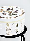 Mit Schmetterling-Motiven beklebte runde Schachtel