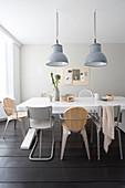 Industrial lights above the dining table with various chairs