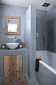 Rustic bathroom in gray with built-in tub and vanity with wooden door