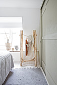 Clothes rack made of branches in a white bedroom