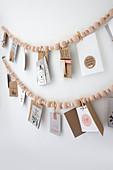 Girlande aus Holzperlenkette mit Postkarten hängen an weißer Wand