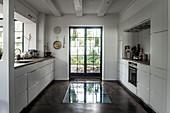 Weiße Einbauschränke vor Fenster und Boden mit Glaseinsatz vor Fenstertür in der Küche