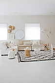 Side table on rug with diamond pattern and couches in light living room