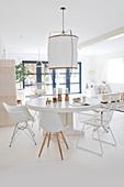 Runder Tisch mit Klassikerstühlen in weißem, offenem Wohnraum