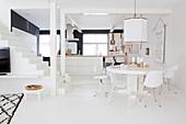 Runder Tisch mit verschiedenen Stühlen vor Kücheninsel und Treppe in weißem, offenem Wohnraum