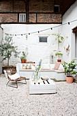 Holzbank, Palettentisch und Stuhl auf Terrasse mit weiß gestrichener Ziegelwand und Kiesboden