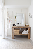 Wooden table with countertop basin in a white corner of the bathroom