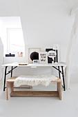 Arbeitsecke mit weißer Tischplatte, schwarz-weißer Dekoration und Holzbank mit Tierfell